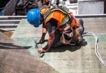 pracujący na dachu budowlaniec