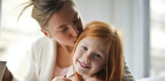 Mama przytulająca i całująca córkę